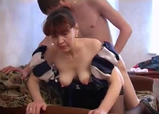 Dress-wearing chick sucks her son's cock